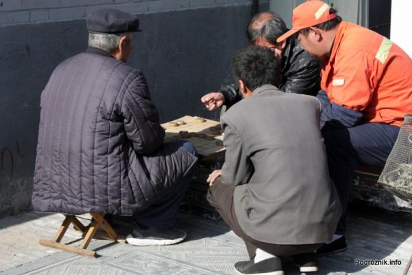 Chiny - Pekin - mężczyźni grający przy stoliku ustawionym na chodniku - kwiecień 2013