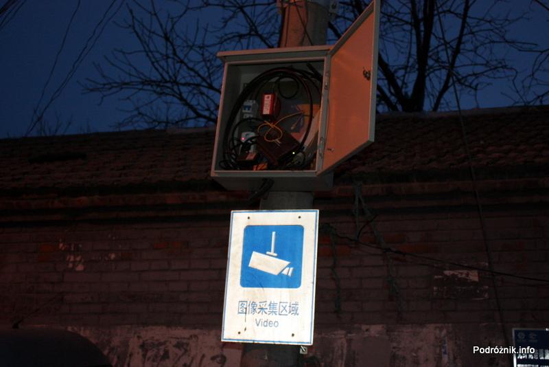 Chiny - Pekin wieczorem - rozbebeszona skrzynka nad znakiem informującym o monitoringu - kwiecień 2013