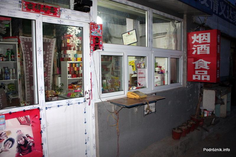 Chiny - Pekin wieczorem - publiczny telefon stojący na ladzie małego sklepu - kwiecień 2013
