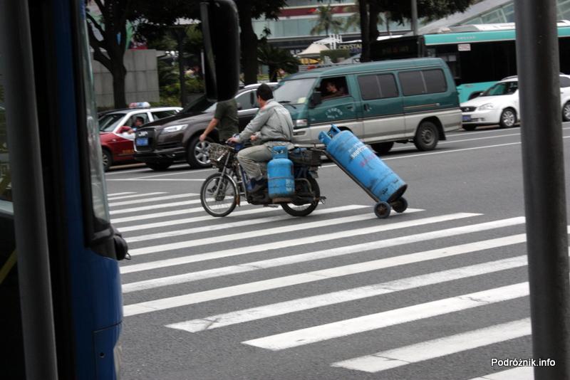 Chiny - Shenzhen - motor z dwoma butlami z gazem i trzecią ciągniętą na wózku - kwiecień 2013