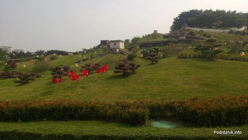 Chiny - Shenzhen - Splendid China Folk Village - budowle na wzgórzu i sztuczne kwiaty na zboczu - kwiecień 2013