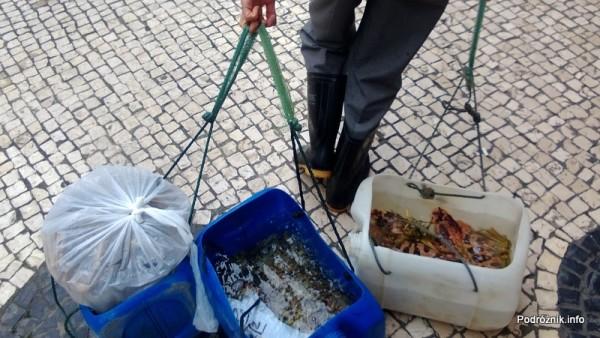 Chiny - Makao - mężczyzna ciągnie pojemniki ze świeżymi owocami morza - kwiecień 2013