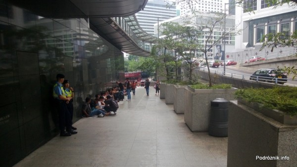 Chiny - Hongkong  - strajkujący pracownicy siedzą pod ścianą budynku - kwiecień 2013
