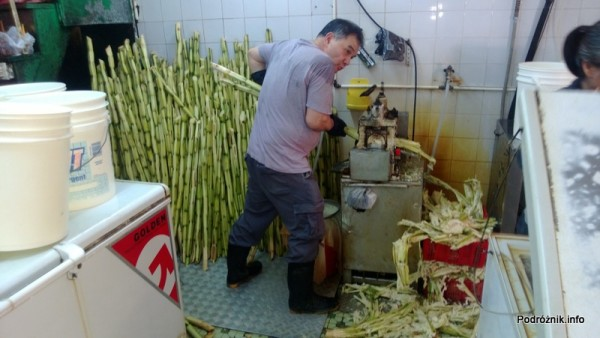 Chiny - Makao - mężczyzna przy elektrycznej prasie do wyciskania soku z trzciny cukrowej - kwiecień 2013