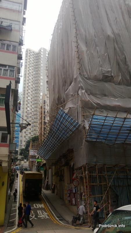 Chiny - Hongkong - bambusowe rusztowanie wokół budynku i trzydziestopiętrowy blok mieszkalny w tle - kwiecień 2013