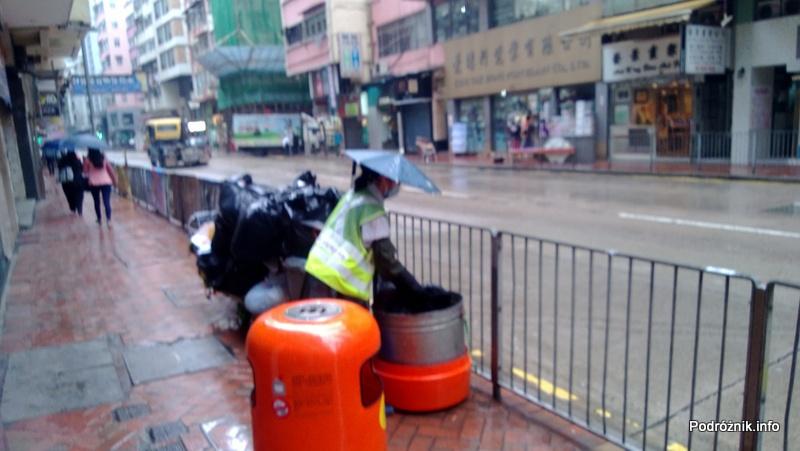 Chiny - Hongkong - pracownik służb miejskich z parasolką na głowie - kwiecień 2013