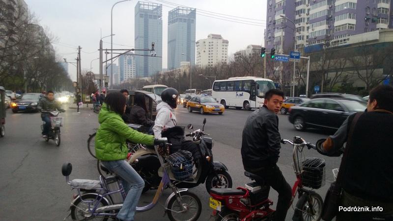 Chiny - Pekin - okolice dworca kolejowego Dongzhimen - ludzie na jednośladach czekający na przejazd - kwiecień 2013