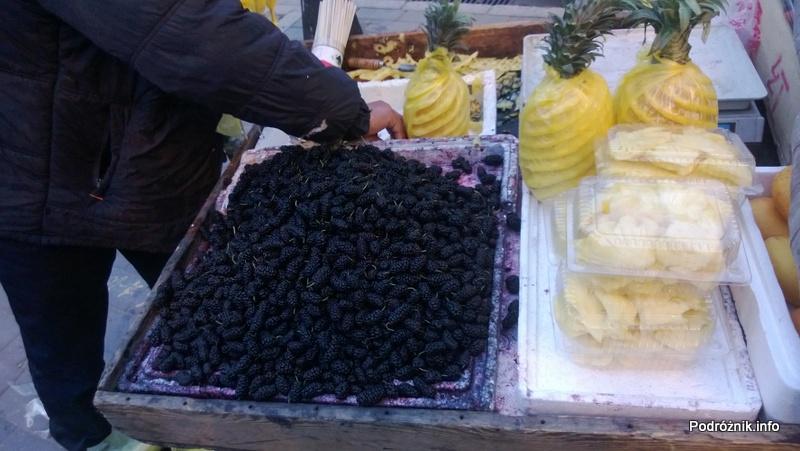 Chiny - Pekin - okolice dworca kolejowego Dongzhimen - stragan z owocami - morwy oraz obrane ananasy - kwiecień 2013